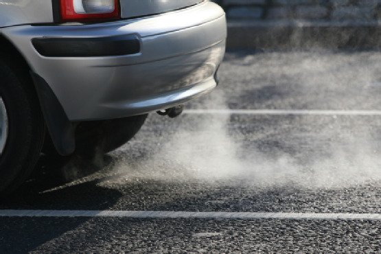Car exhaust fumes coming from automobile polluting city air